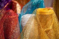 发光的五颜六色的东方柔滑的纺织品。 免版税库存照片