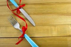 发光的叉子和刀子有丝带的在木背景 免版税图库摄影