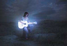 发光的吉他在晚上 库存图片
