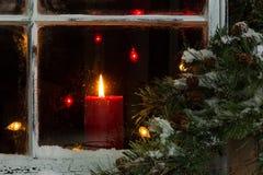 发光的圣诞节蜡烛在结霜的家庭窗口里 免版税库存照片