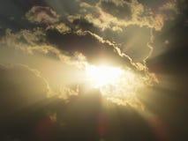 发光的太阳捉迷藏后边在土块在一多云天,面对直接地对在太阳天时间的照相机 免版税库存照片