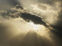 发光的太阳捉迷藏后边在土块在一多云天,面对直接地对在太阳天时间的照相机 库存照片