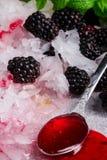 发光的寒冷被击碎的冰的宏观图片 冰用黑莓、匙子、莓果糖浆和薄荷叶 夏天成份 库存图片