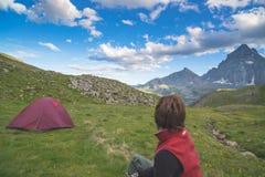发光的山峰庄严看法在日落的高在阿尔卑斯 看看法,在backg的焦点的一个人背面图  库存照片