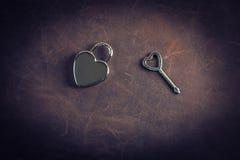 发光的心脏形状锁和钥匙在Nubuck用皮革包盖背景 免版税库存照片