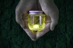 发光的瓶子在手上 库存图片