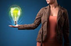 发光的电灯泡在妇女的手上 图库摄影