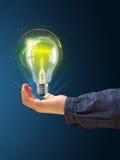 发光的电灯泡在妇女的手上 免版税库存图片