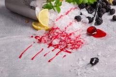 发光的白色冰块顶视图  冰用成熟黑莓、柠檬、点心用匙和莓果糖浆在一块灰色石头 免版税库存图片