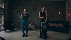 发光的礼服的可爱的爵士乐歌唱者在与萨克斯管吹奏者舞蹈的阶段 股票录像