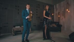 发光的礼服的爵士乐歌唱者在阶段执行与萨克斯管吹奏者在蓝色服装 股票录像