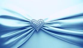 发光的蓝色缎丝带和金刚石心脏 库存图片