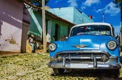 发光的蓝色经典老美国汽车和典型的五颜六色的殖民地大厦在特立尼达 库存照片