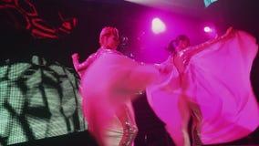 发光的衣服的性感的时髦的女孩在党跳舞在阶段的夜总会 光 影视素材