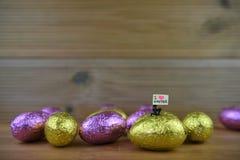 发光的被包裹的巧克力复活节彩蛋和微型人有标志的为爱复活节上 免版税库存图片