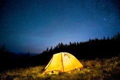 发光的野营的帐篷在夜山森林里在满天星斗的天空下 库存照片