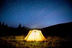 发光的野营的帐篷在夜山森林里在满天星斗的天空下 库存图片