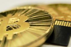 发光的金子Bitcoin硬币和microSD存储卡万客隆细节  免版税图库摄影