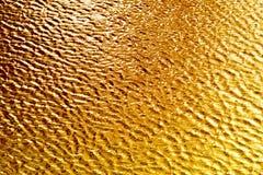 发光的金映象点加点了背景,金黄波纹纹理,黄色闪烁墙纸, 库存照片