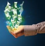 发光的金钱在商人的手上 免版税图库摄影