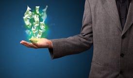 发光的金钱在商人的手上 免版税库存图片