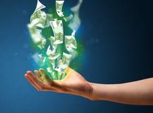 发光的金钱在商人的手上 库存图片