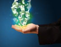 发光的金钱在商人的手上 免版税库存照片
