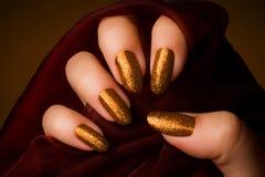 发光的金黄钉子修指甲 免版税库存图片