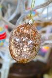 发光的闪光金黄东部装饰品由从白色分支的一根金绳子垂悬与被弄脏的其他五颜六色的蛋装饰品后边 库存照片