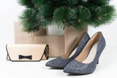 发光的鞋和一个小袋子,立场在圣诞树下 库存照片