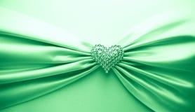 发光的绿色缎丝带和金刚石心脏 库存照片