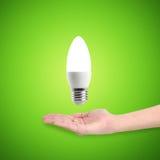 发光的LED节能电灯泡在手上 库存图片