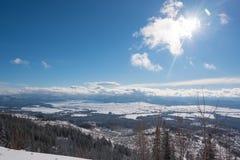 发光美丽的太阳,虽然在雪盖的谷的一朵云彩 免版税库存图片