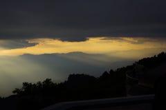 发光通过云彩的太阳 免版税库存图片