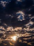 发光通过灰色云彩的太阳 免版税库存图片