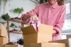 发动小企业主在箱子的包装鞋子在workpl 免版税库存照片