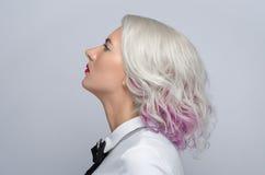 头发和构成题材:有称呼与在灰色背景的红色嘴唇的创造性的头发的美丽的年轻白肤金发的妇女在演播室 免版税库存照片