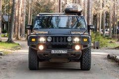 黑发嗡嗡声的东西H2车在肮脏的乡下公路去 图库摄影
