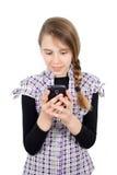 发在她的手机的年轻微笑的女孩正文消息隔绝在白色 免版税图库摄影