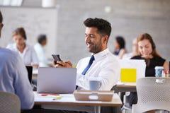 发在手机的商人正文消息在办公室 免版税库存照片