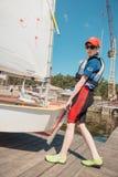 发射在水的年轻男孩小风船 免版税库存照片