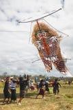 发射巨大的风筝的巴厘语少年 免版税图库摄影