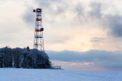 发射机和天线在电信在多雪的国家耸立,日落 免版税图库摄影