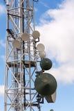 发射机和天线在电信耸立与多云蓝天 图库摄影
