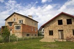 发展的土地在农村邻里 两个新的不完成的砖家庭村庄房子划分了与在summ的临时篱芭 库存图片