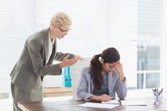 发布命令的女实业家在她的工友 免版税图库摄影