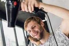 发廊的少妇 有吹风器的英俊的男性美发师干毛发 库存照片