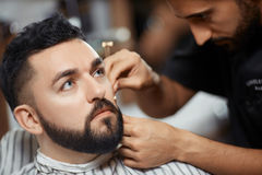 发式专家与剃刀的切口面包客户的 库存图片