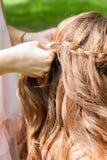 发式专家对室外的女孩的编织猪尾 创造辫子 库存照片
