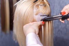 头发引伸做法 美发师对头发引伸做女孩,白肤金发在美容院 选择聚焦 库存图片